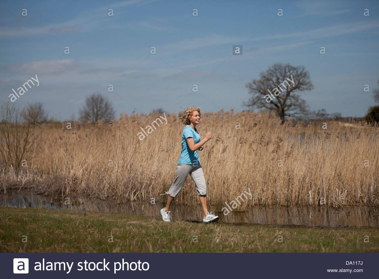 Una donna matura power walking in campagna Immagini Stock