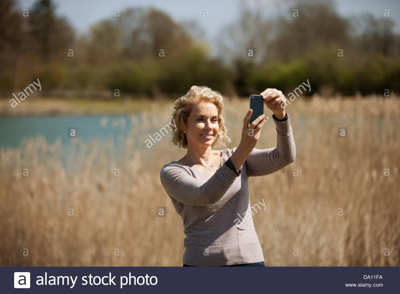 Una donna matura in campagna, prendendo una foto con uno smartphone Immagini Stock