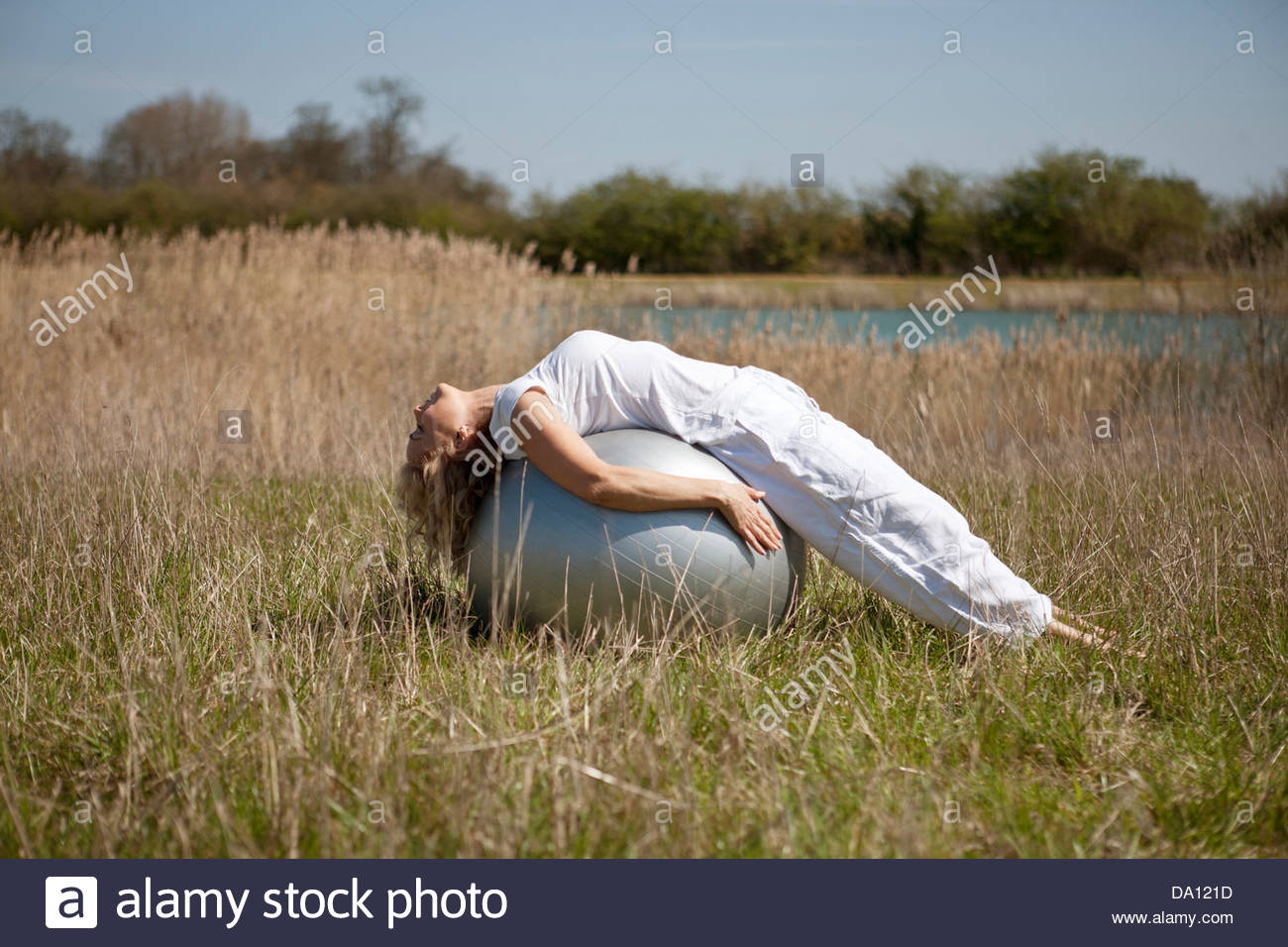 Una donna matura stretching su una palla ginnica Immagini Stock