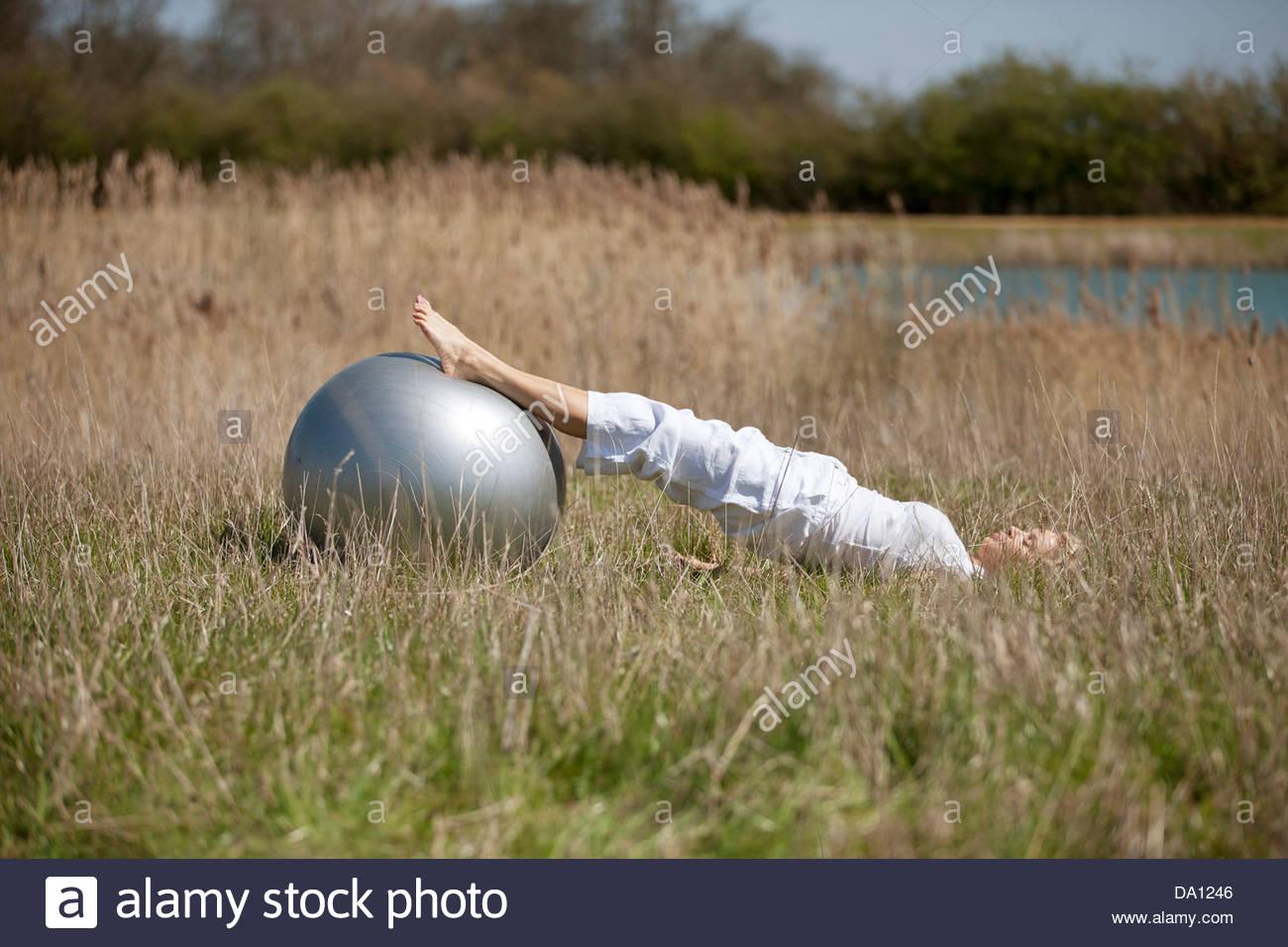 Una donna matura esercitando con una palla ginnica Immagini Stock