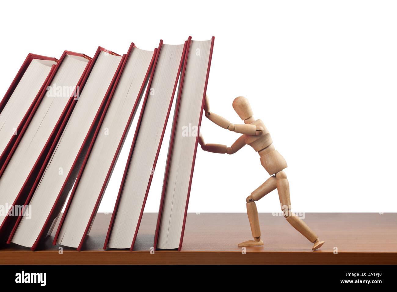 Figurina cercando di fermare un effetto domino causato dalla caduta di libri Immagini Stock