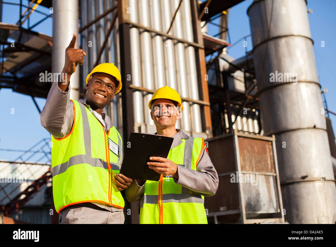 Allegro chimica del combustibile i lavoratori che operano in impianti di raffineria Immagini Stock