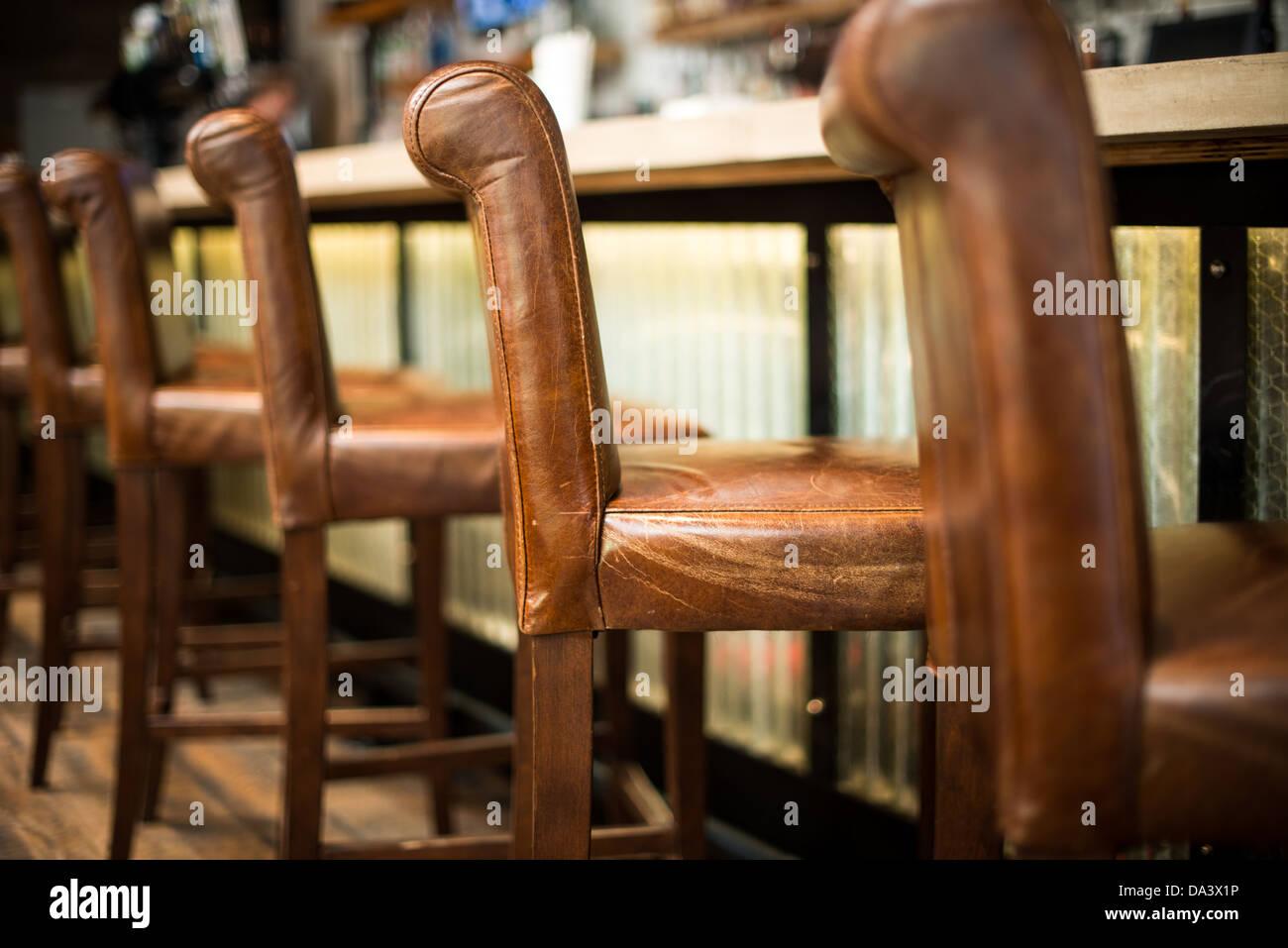 Una fila di pelle marrone sgabello da bar sedie allineate accanto