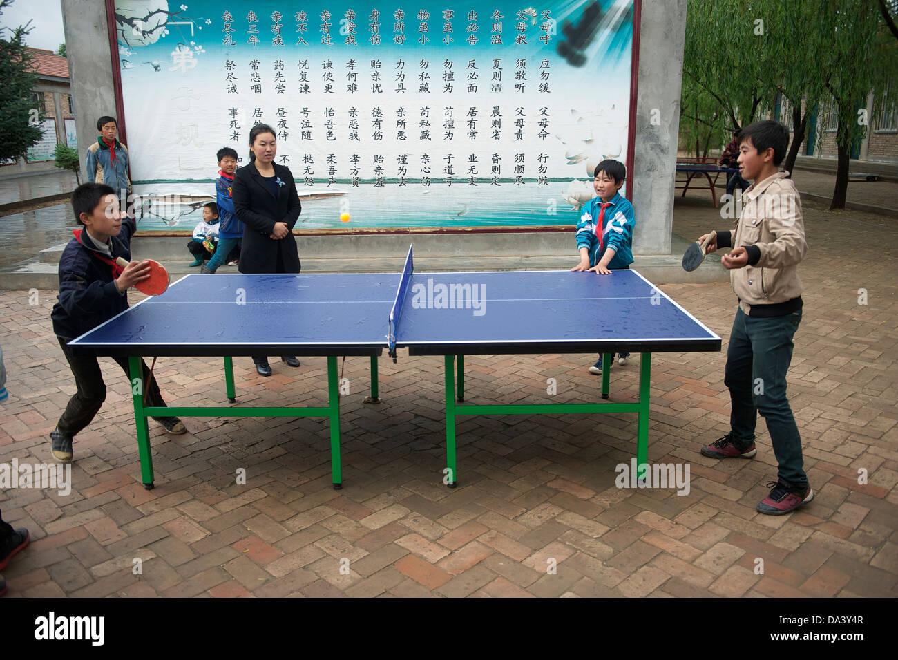Studenti della scuola primaria giocare a ping pong in Haiyuan, Ningxia Hui regione autonoma della Cina. 21-Maggio Immagini Stock
