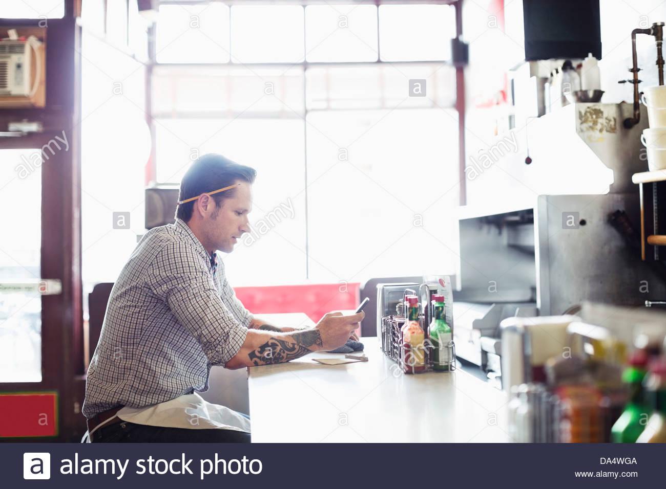 Maschio proprietario di affari di messaggistica di testo sul telefono cellulare al contatore in diner Immagini Stock