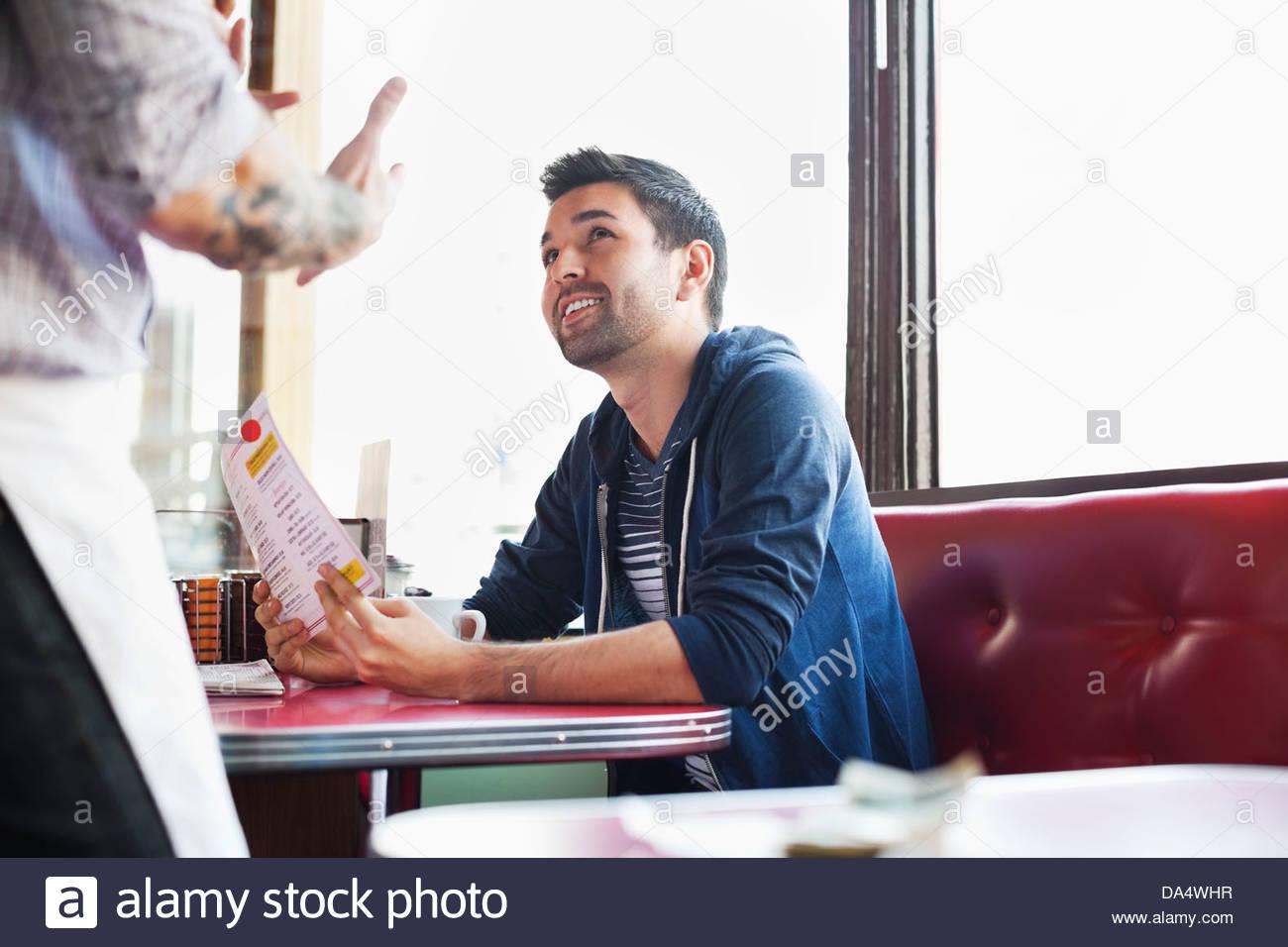 Maschio di cliente di ordinare cibo in diner Immagini Stock