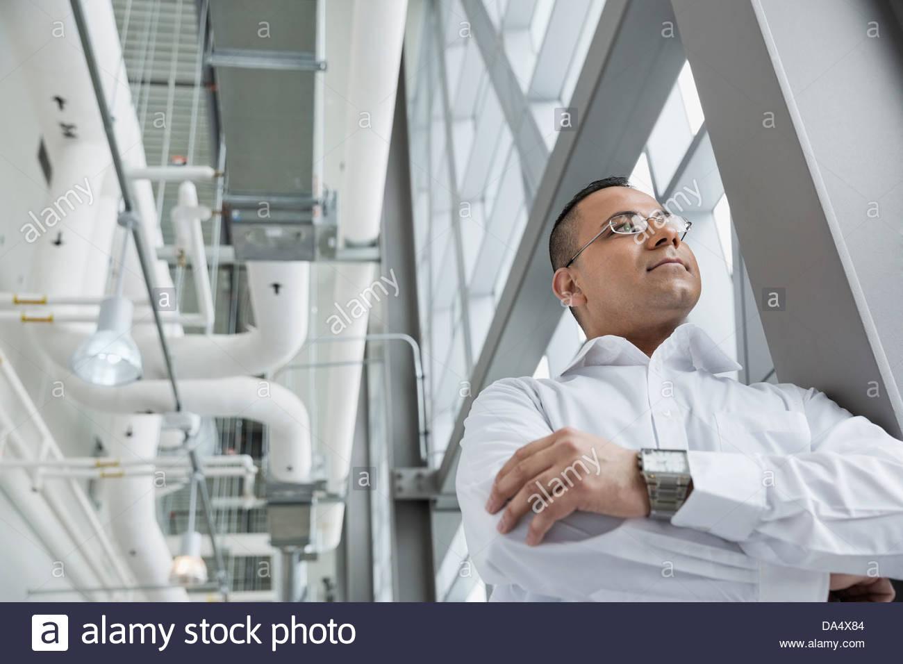 Basso angolo di visione di imprenditore in piedi in edificio per uffici Immagini Stock