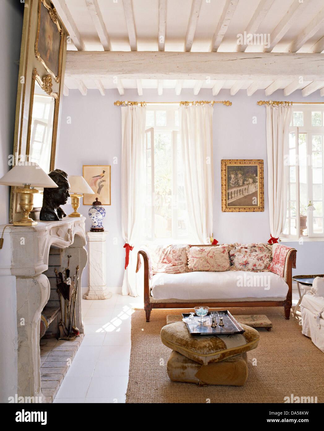 https://c8.alamy.com/compit/da58kw/cuscini-pianale-accanto-al-camino-in-blu-pallido-paese-francese-soggiorno-con-divano-di-antiquariato-e-dipinti-di-bianco-travi-a-soffitto-da58kw.jpg