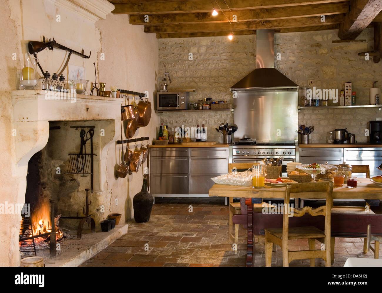 Acceso il fuoco nel camino in cucina di paese con rustici tavoli e ...