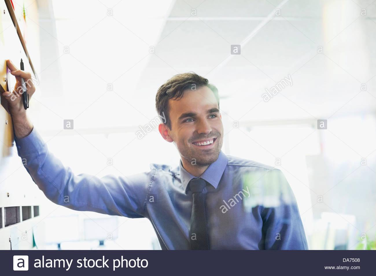 Imprenditore sorridente allegando una nota adesiva alla parete Immagini Stock