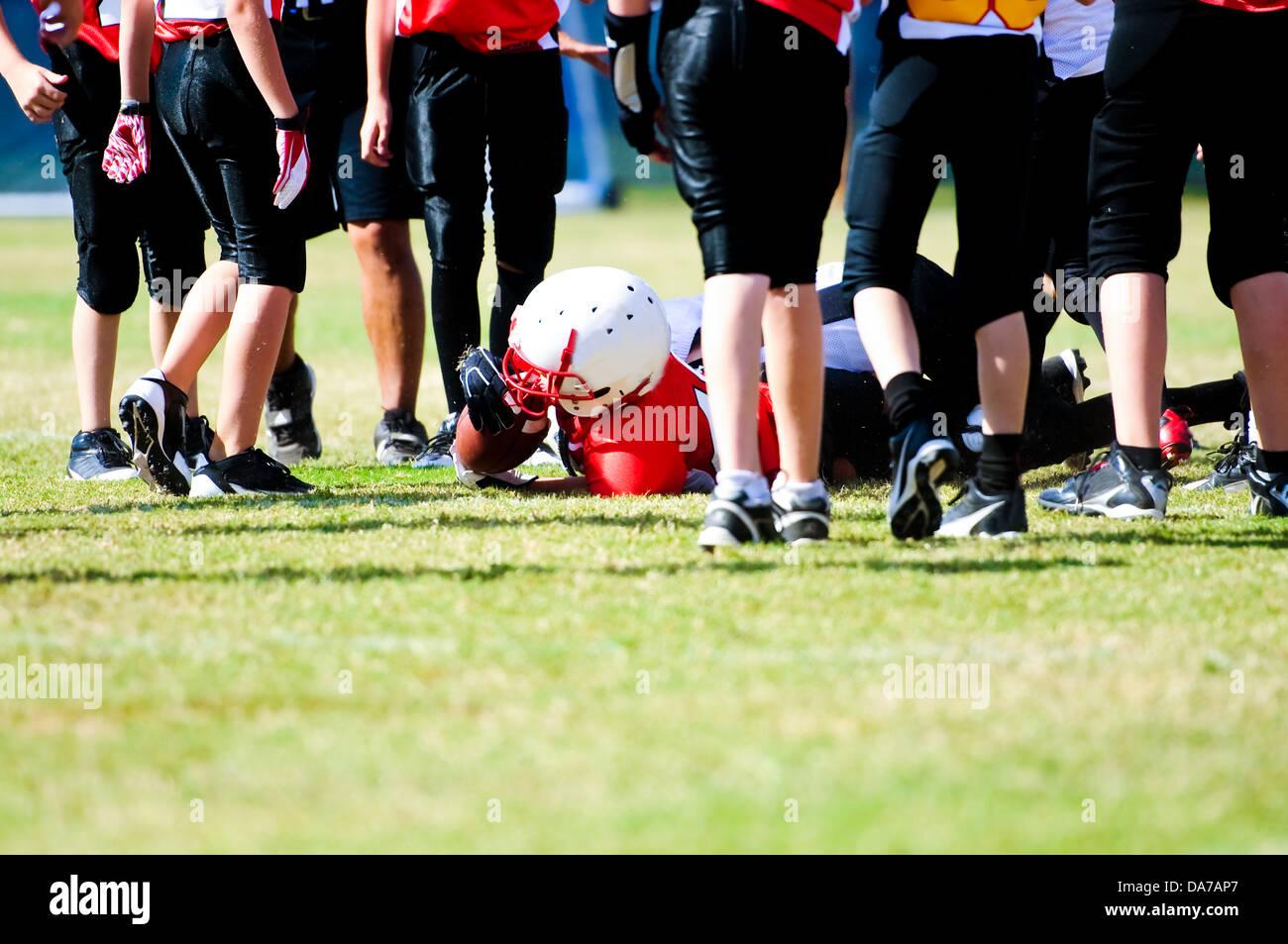 Affrontato il calcio ragazzo in mezzo ad un gruppo di giocatori. Immagini Stock