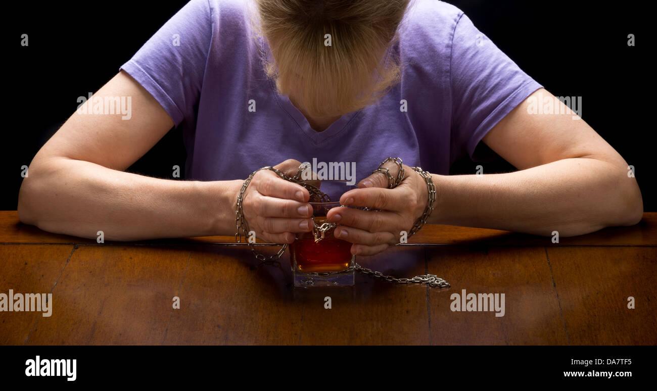 Concetto photo closeup per alcolismo malattia che mostra le mani incatenato al bicchiere di whiskey con testa di Immagini Stock