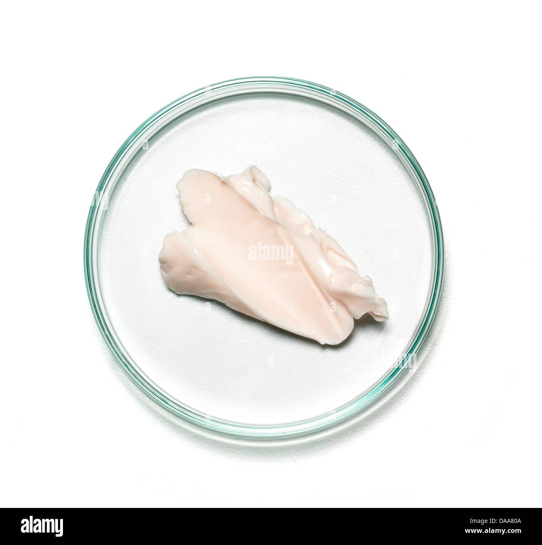 Rosa beige crema corpo su una capsula di petri ritagliato su uno sfondo bianco Immagini Stock