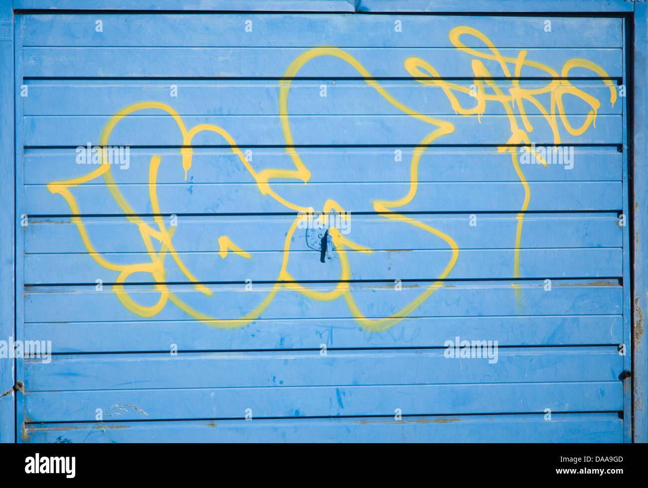 Graffiti spruzzato su blu porta di garage Immagini Stock