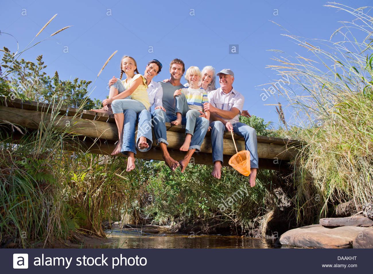 Ritratto di sorridere multi-generazione famiglia seduta a piedi nudi sulla passerella sul torrente Immagini Stock