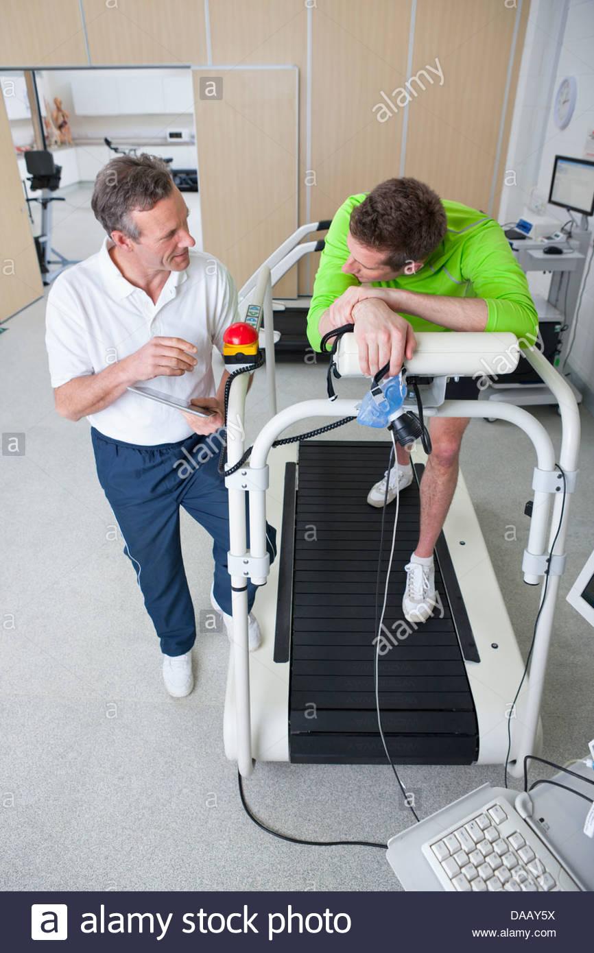 Sport scienziato parlando a runner con maschera sul tapis roulant in laboratorio Immagini Stock