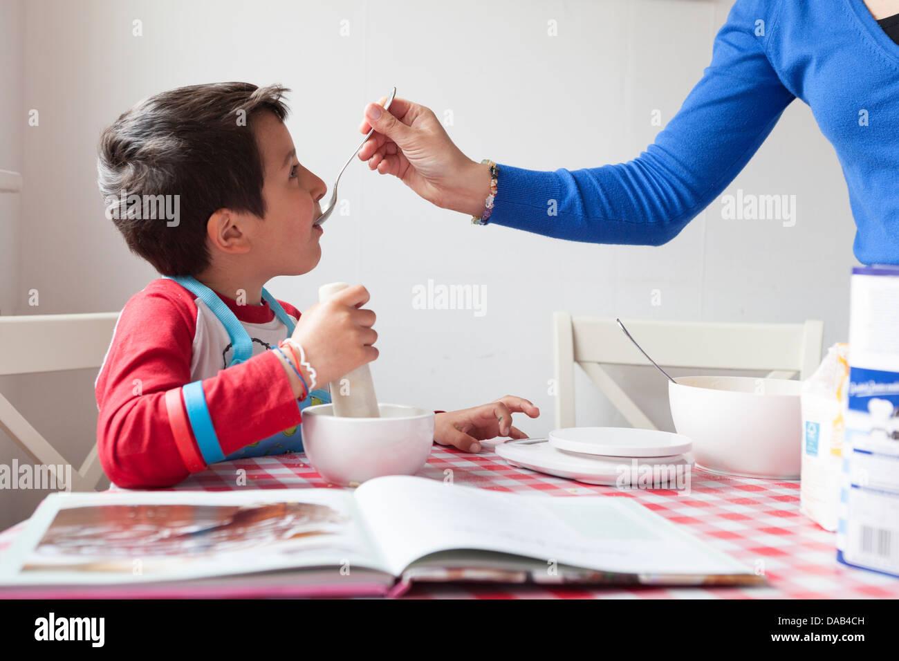 Madre e figlio giovane cucinare insieme-degustazione del cibo Immagini Stock