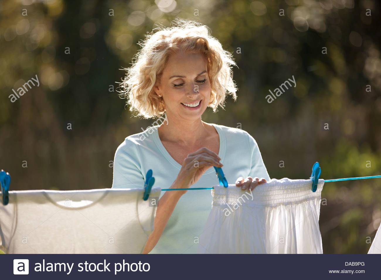 Una donna matura ancoraggio fuori lavaggio su una linea di lavaggio, sorridente Immagini Stock