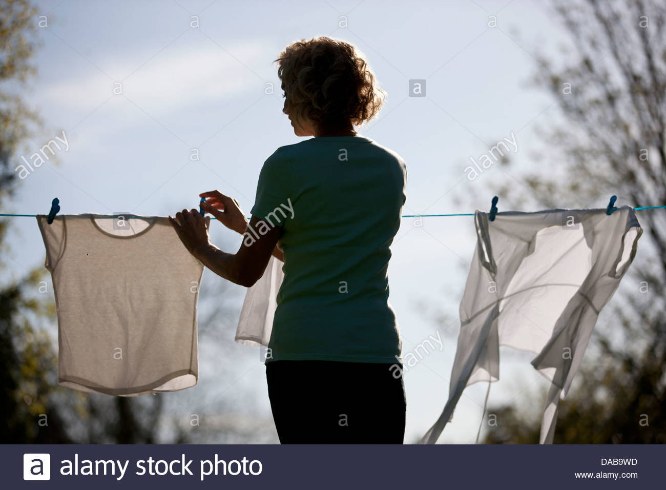 Una donna matura ancoraggio fuori lavaggio su una linea di lavaggio, vista posteriore Immagini Stock