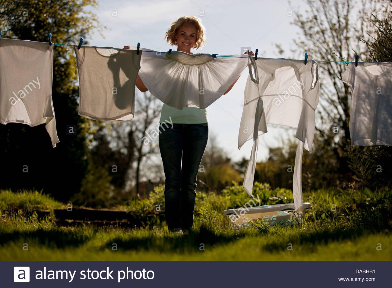 Una donna matura ancoraggio fuori lavaggio su una linea di lavaggio, vista frontale Immagini Stock