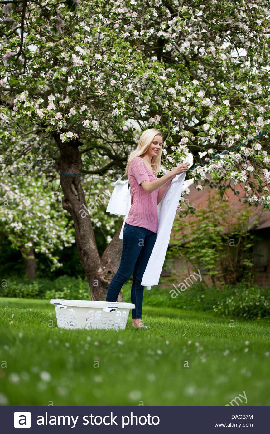 Una giovane donna appendere fuori il lavaggio in primavera Immagini Stock
