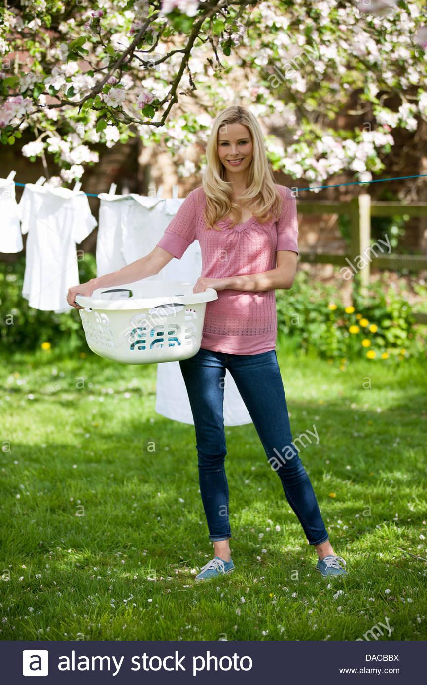 Una giovane donna in possesso di un cestello di lavaggio nella parte anteriore di una linea di lavaggio Immagini Stock