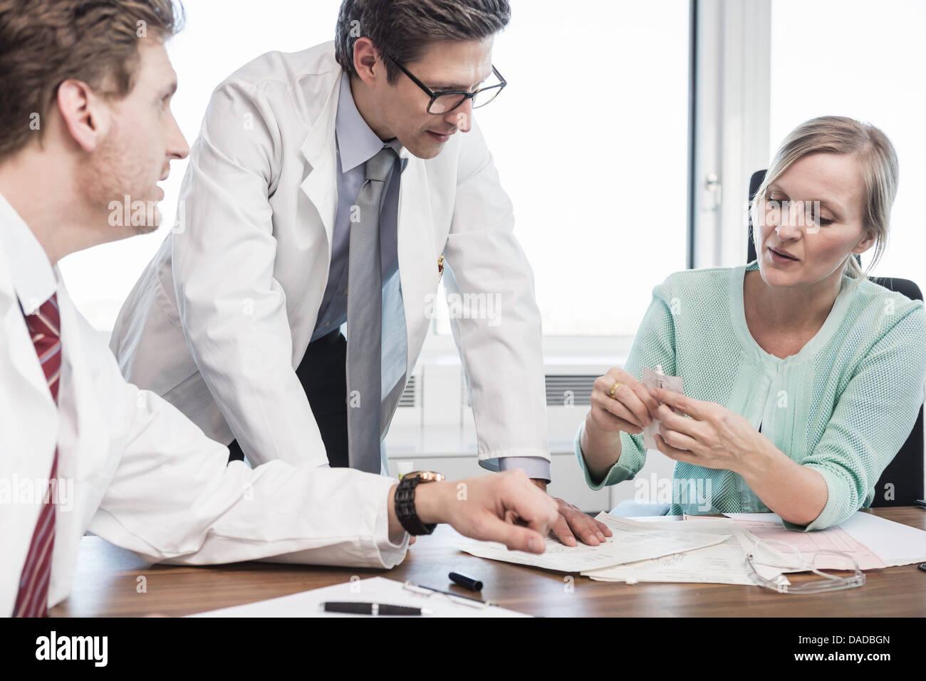 Gli uomini indossano camici da laboratorio parlando di donna sat alla scrivania tenendo il tubo di prova Immagini Stock