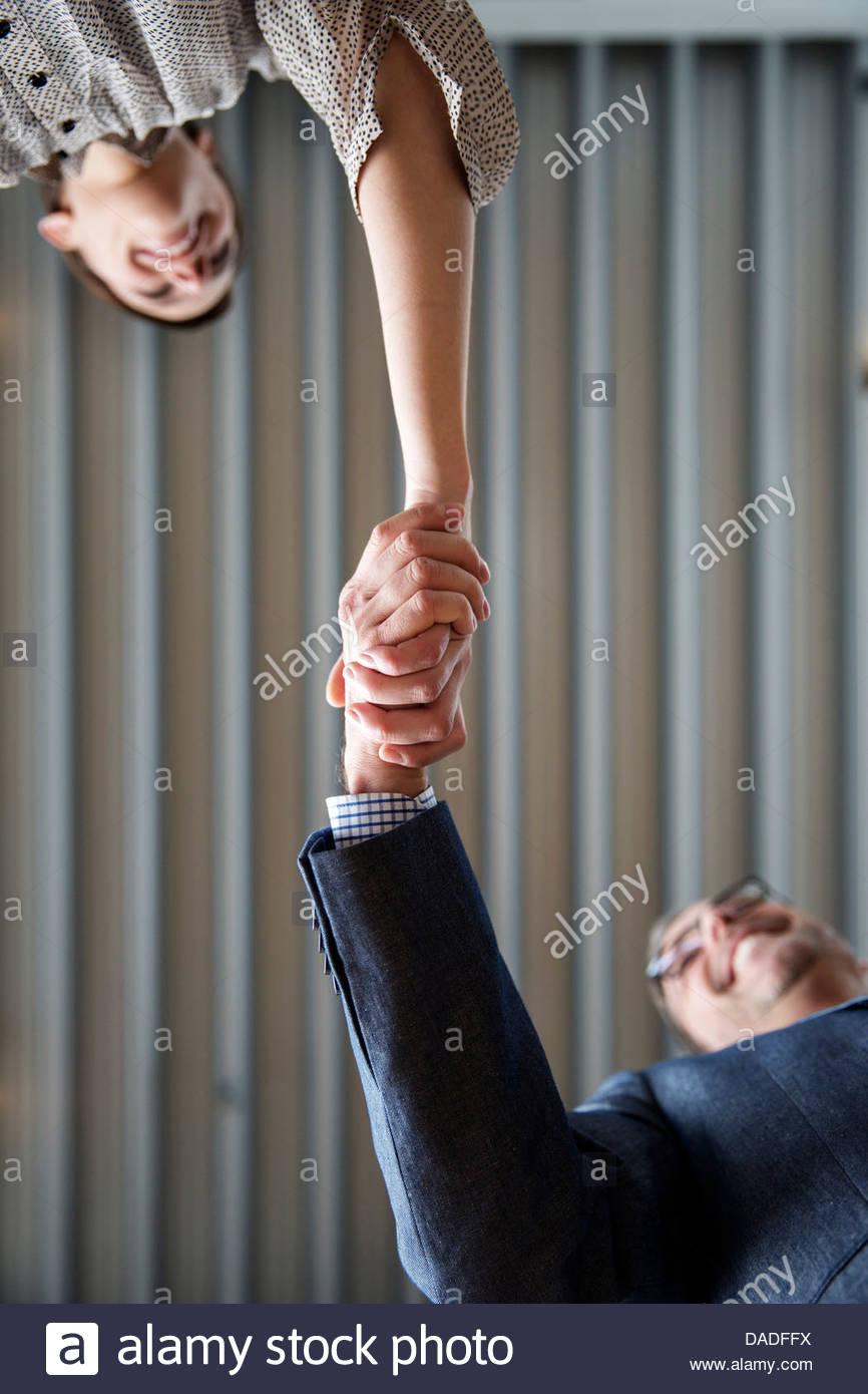 L uomo e la donna si stringono la mano Immagini Stock