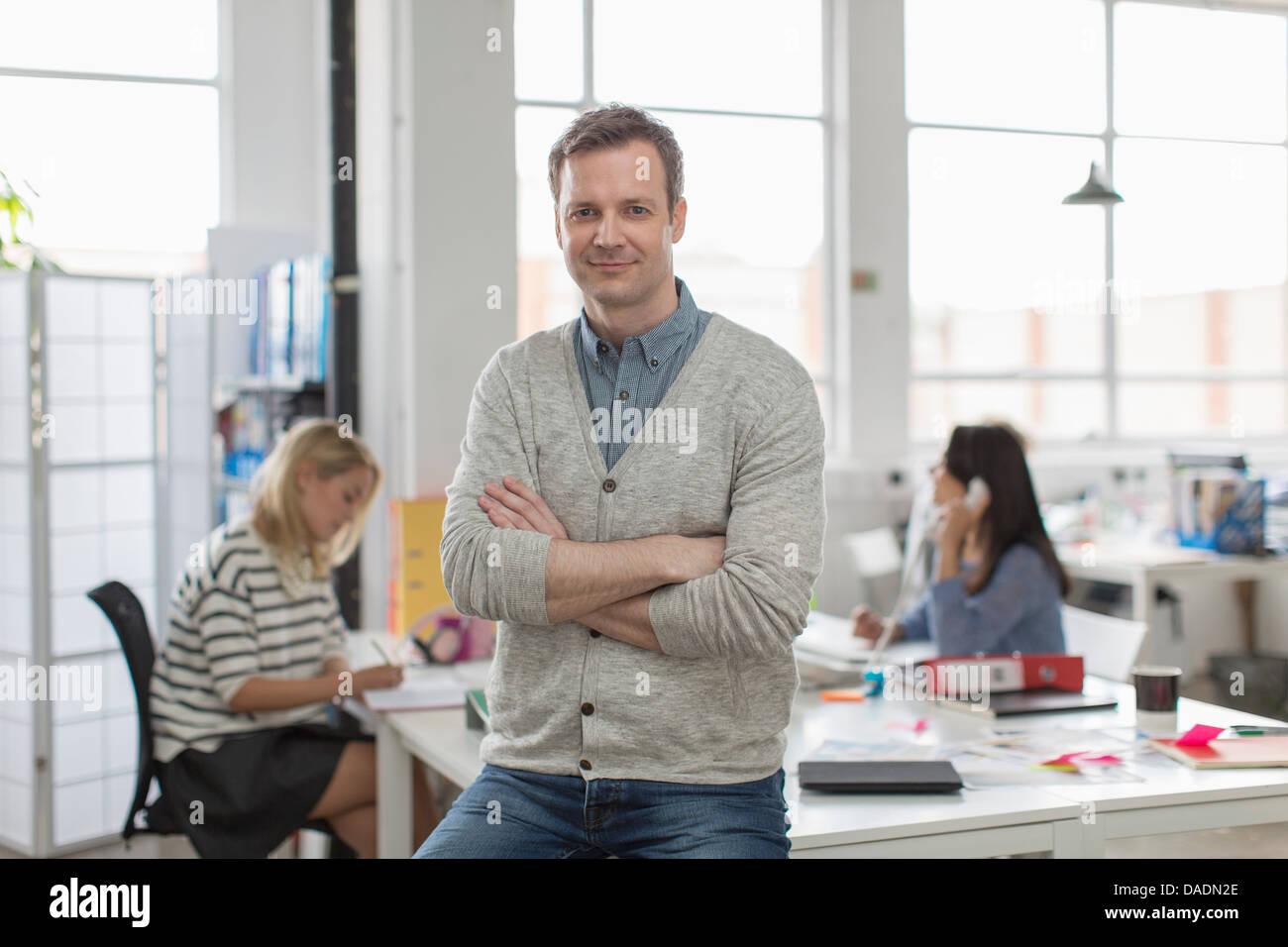 Uomo maturo seduto sulla scrivania e sorridente in ufficio creativo, ritratto Foto Stock