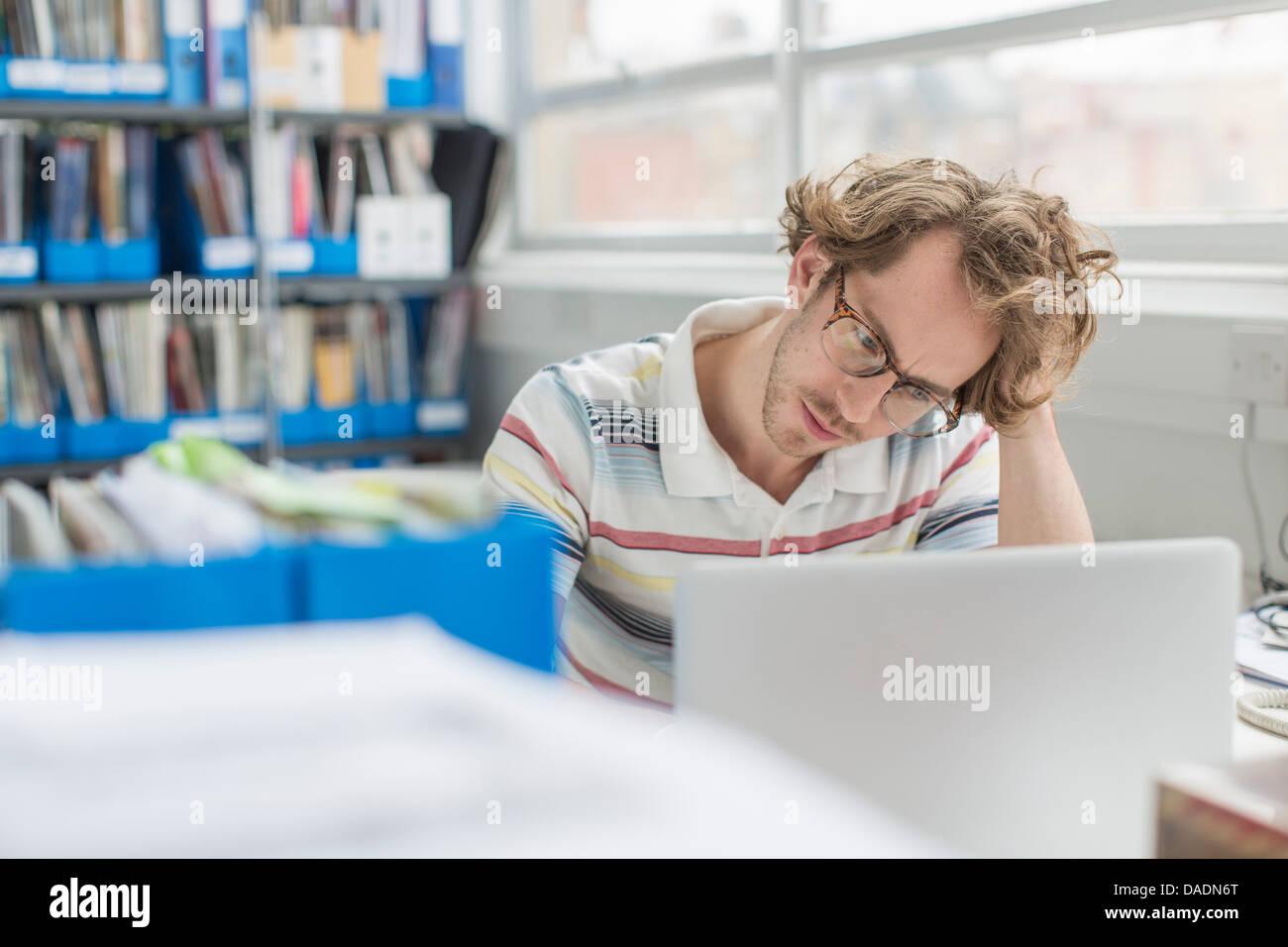 Giovane uomo con testa in mani in ufficio creativo Immagini Stock
