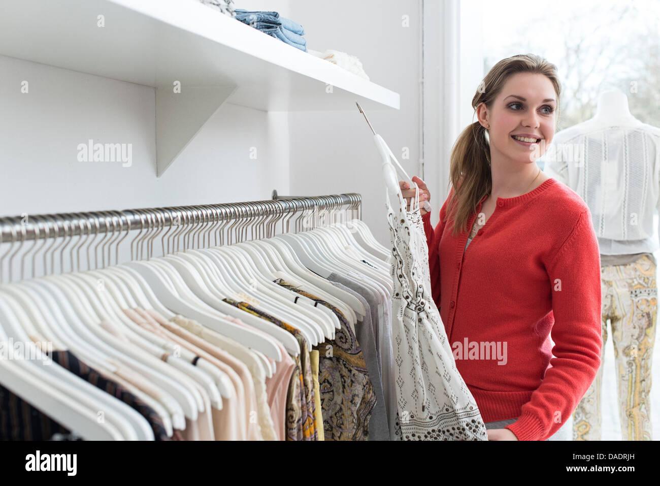 Giovane donna scegliendo abito in negozio di moda Immagini Stock