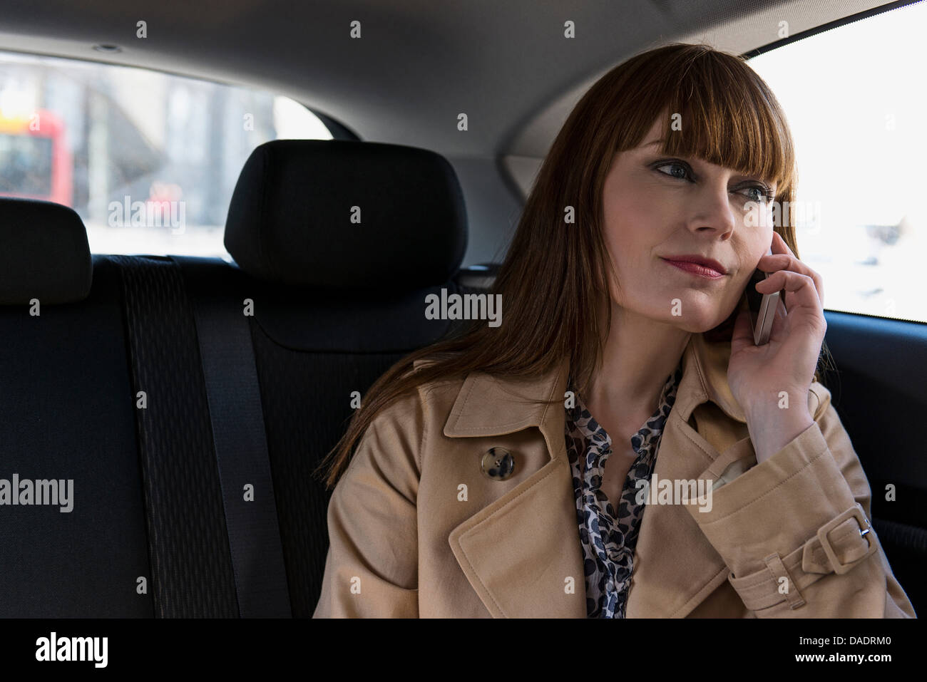 Business donna con telefono cellulare in auto Immagini Stock