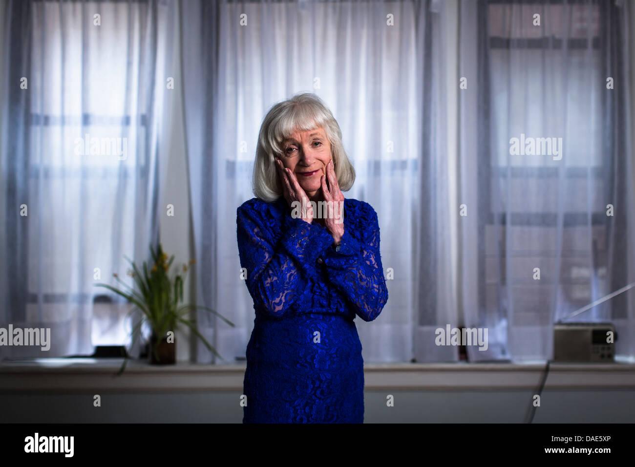 Senior donna in vestito blu con le mani sul viso Immagini Stock