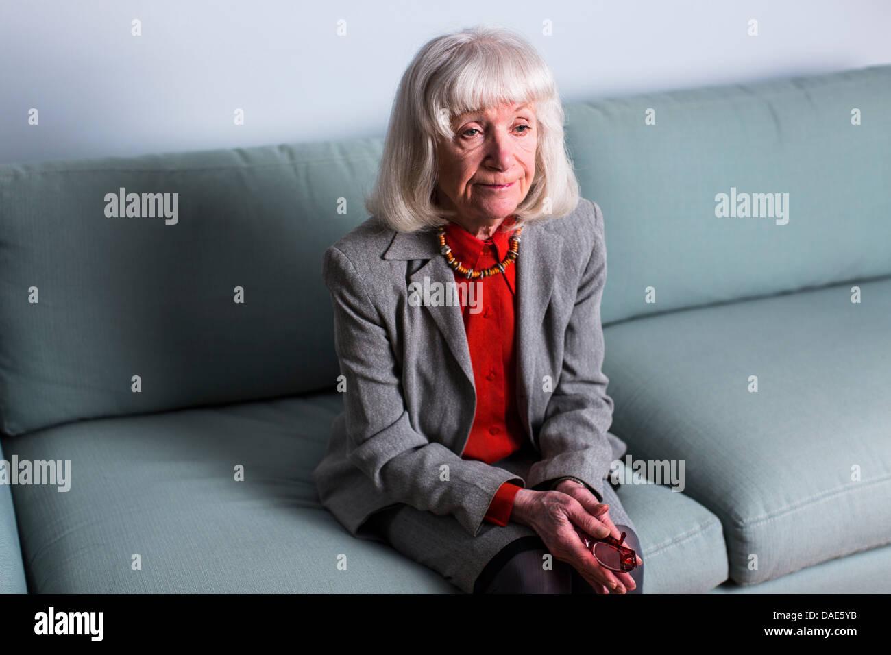 Senior donna seduta su un divano con espressione vuota Immagini Stock