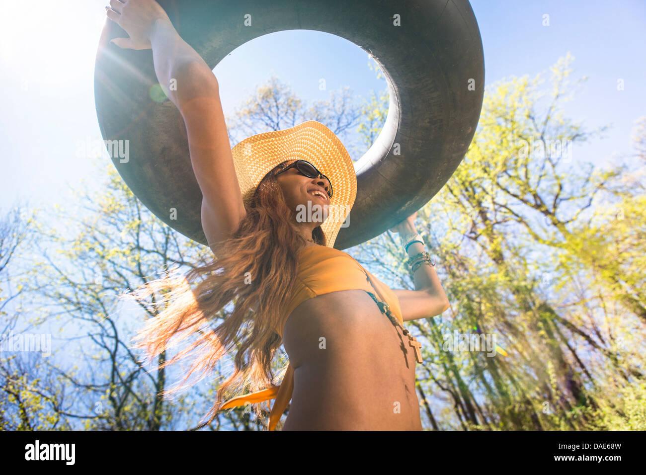 Donna che indossa un cappello e occhiali da sole che porta tubo interno  sopra la testa 8153d32b163e