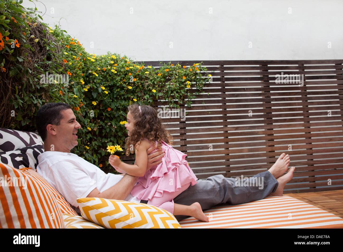 Padre e figlia di relax all'aperto, ragazza con fiori Immagini Stock