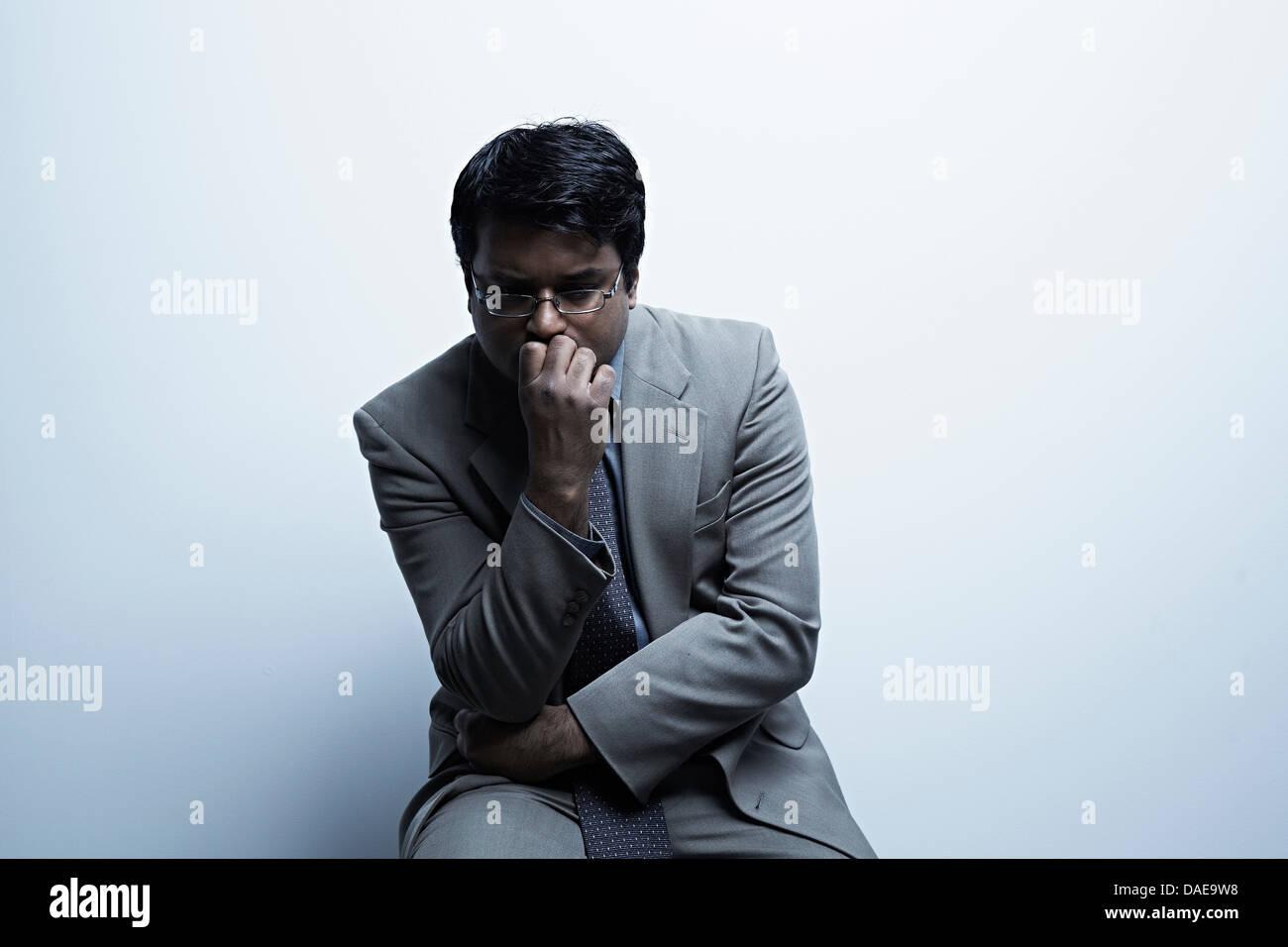 Ritratto in studio di imprenditore con la mano sulla bocca Immagini Stock
