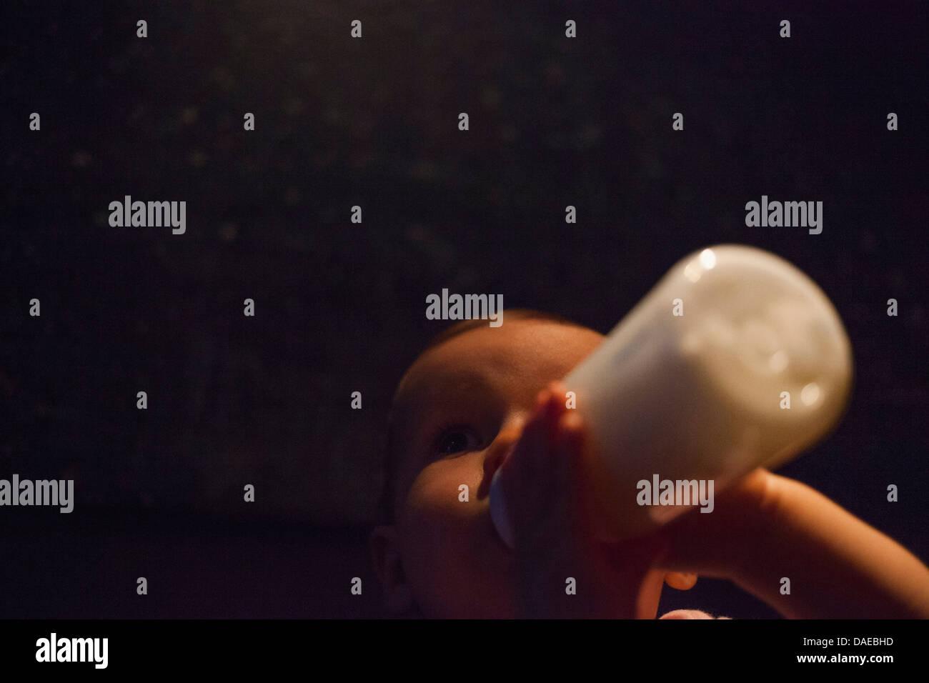 Baby girl alimentazione dalla bottiglia nelle tenebre Immagini Stock