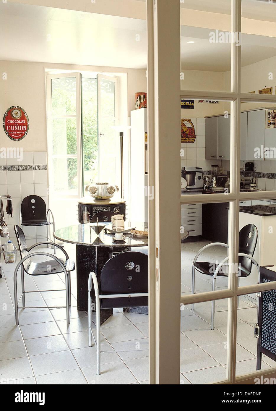 Vetro della porta vetrata aperta a in piastrelle bianche con cucina ...