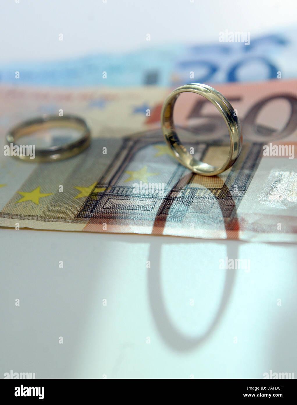 Due anelli di nozze e le banconote in euro giacciono su un tavolo a Berlino, Germania, 11 febbraio 2011. La Corte Immagini Stock
