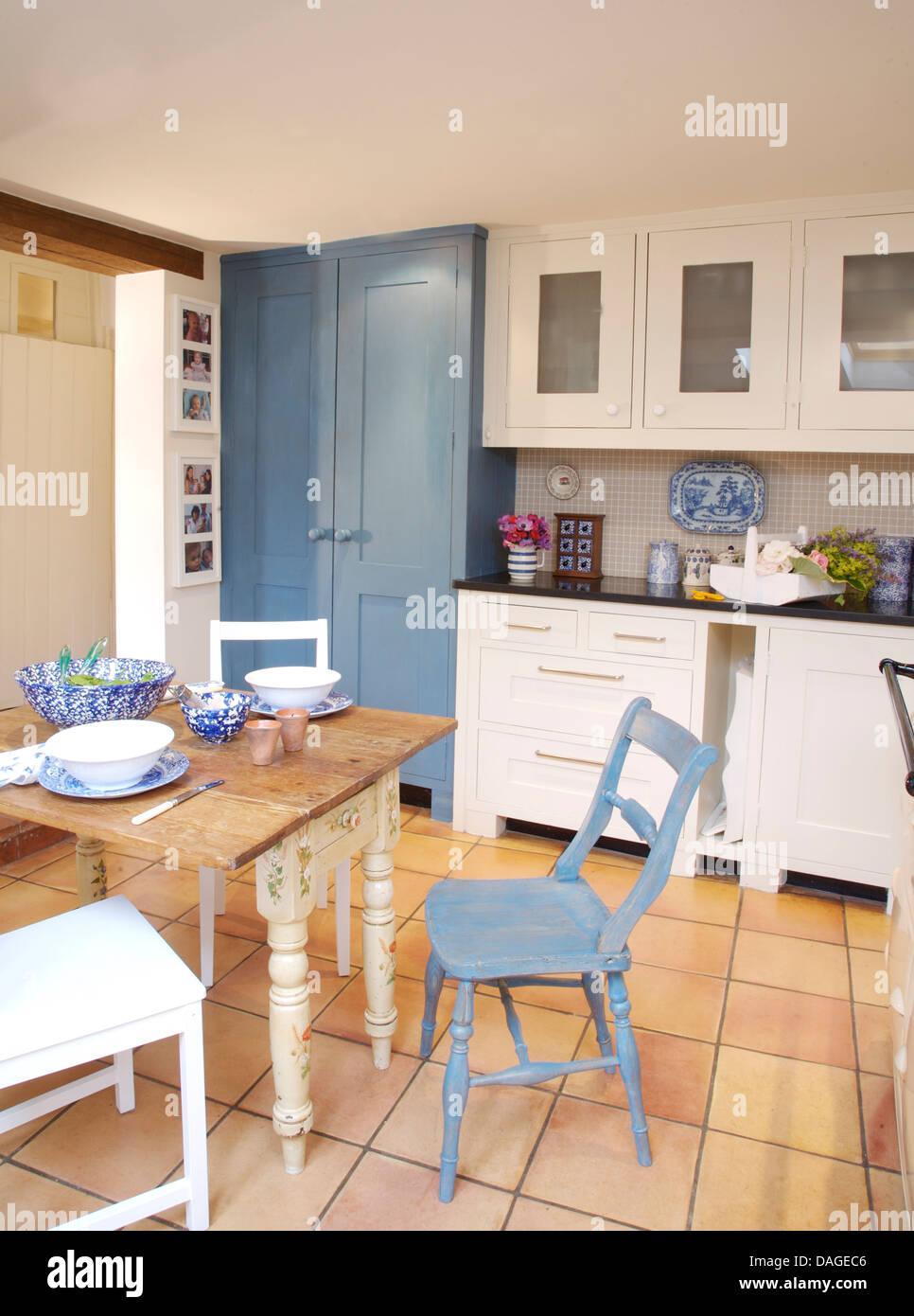 Dipinto di blu sedia accanto alla vecchia tavola dipinta di bianco ...