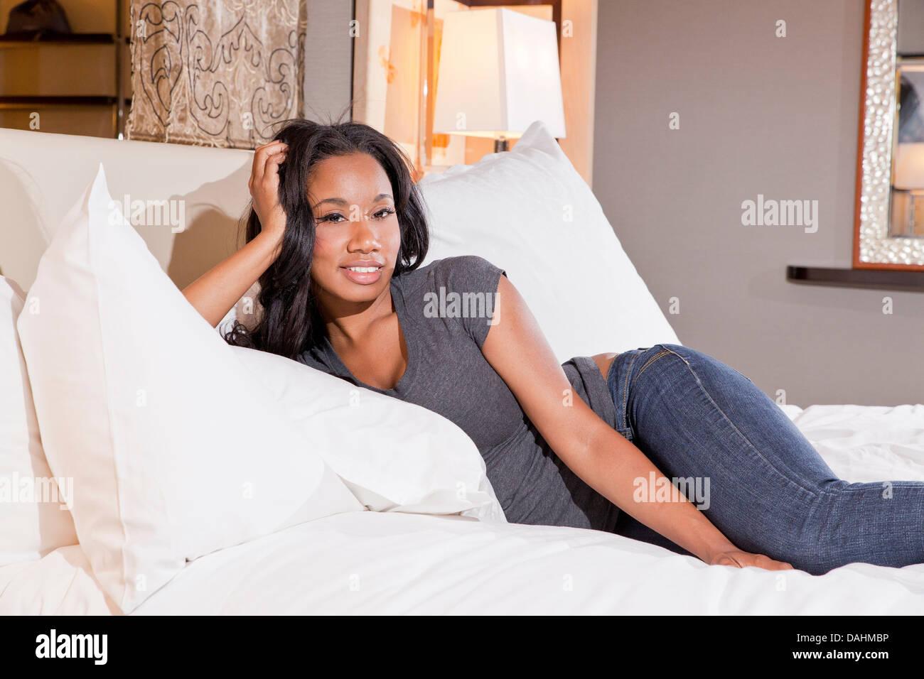 Giovane africano donna americana di riposo in un letto Immagini Stock