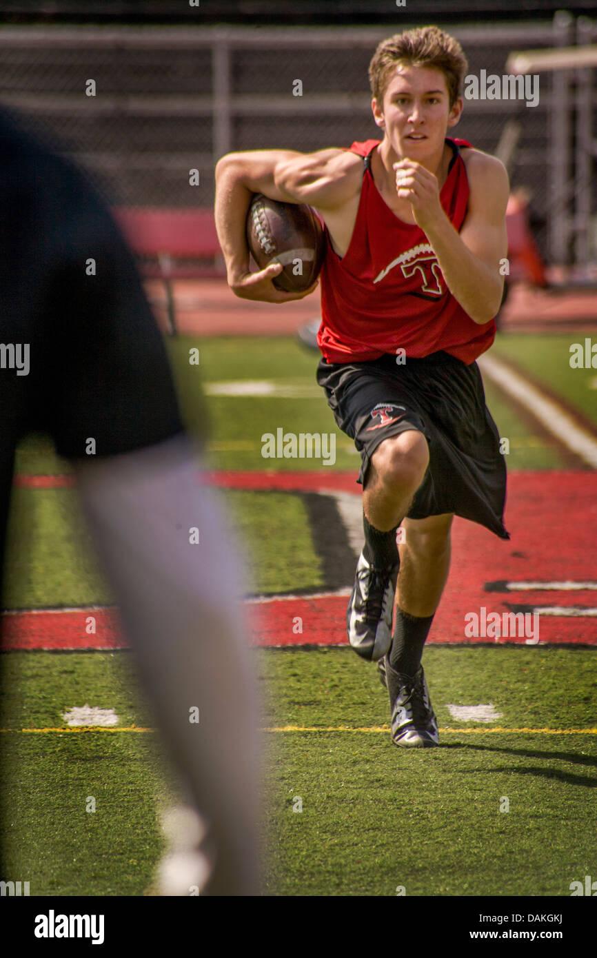Un muscolare e determinato di alta scuola atleta corre con la palla durante la primavera pratica di gioco del calcio Immagini Stock