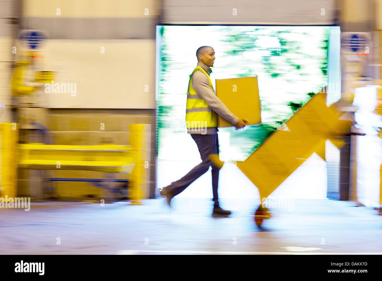 Vista offuscata dei lavoratori che trasportano scatole in magazzino Foto Stock