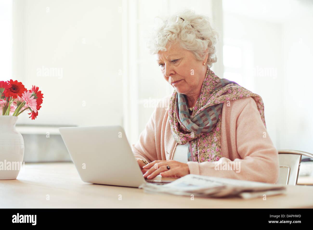 Donna anziana a casa digitando qualcosa usando il suo computer portatile Immagini Stock