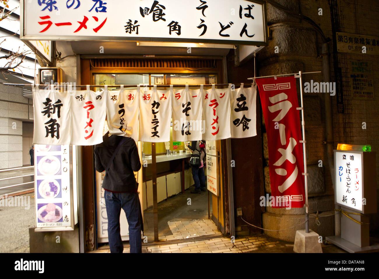 Uomo in piedi fuori il giapponese fast food, Tokyo Giappone Immagini Stock