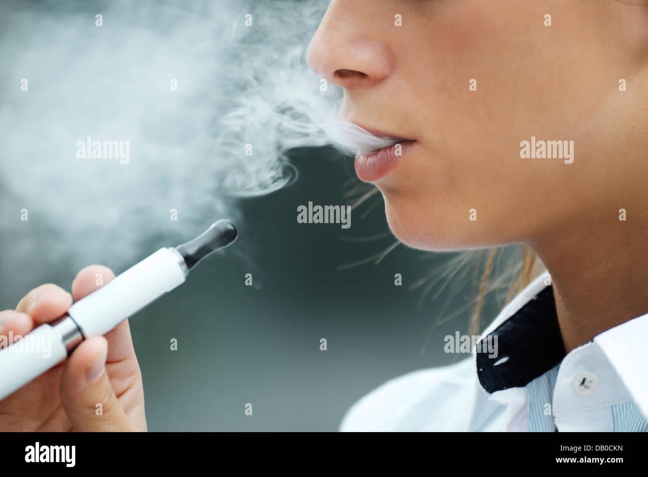 Primo piano della donna e fumo di sigaretta e godendo di fumo. Spazio di copia Immagini Stock
