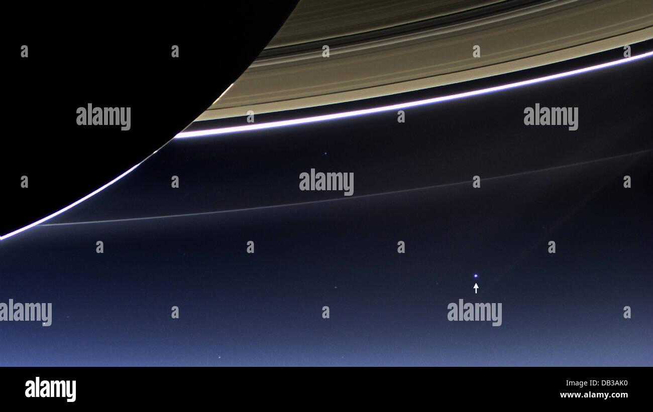Un ampio angolo di visione del pianeta Terra, annotata con una freccia, da sotto gli anelli di Saturno catturato Immagini Stock