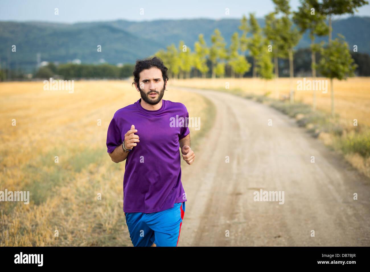 Atletica Giovane uomo che corre nella natura Immagini Stock