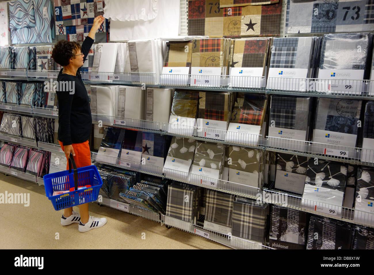 Una donna shopping per il letto di abbigliamento e di fogli. Ullared shopping mall, Svezia. Immagini Stock